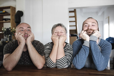 Portrait of adult sons with senior mother sitting at table at home with head in hands - KMKF00980