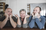 Portrait of adult sons with laughing senior mother sitting at table at home with head in hands - KMKF00983