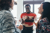 Friends talking at party in loft office - CUF51288