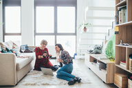 Girlfriends talking and using smartphone on floor in loft office - CUF51291