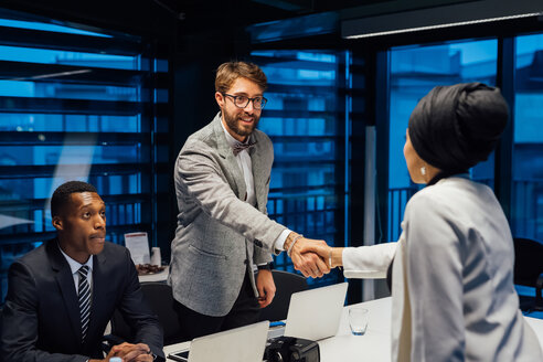 Businessman and female client shaking hands over conference table meeting - CUF51312