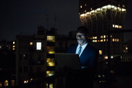 Young businessman using laptop on office balcony at night - CUF51336