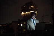 Mid adult businessman typing on laptop on office balcony at night - CUF51342