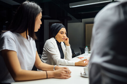 Businesswomen listening at conference table meeting - CUF51354