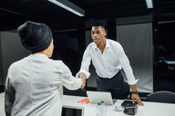 Businessman and woman shaking hands over conference table - CUF51357