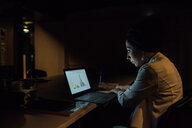 Young businesswoman in office at night looking at laptop - CUF51360