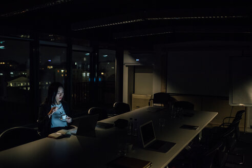 Young businesswoman in office at night looking at laptop - CUF51363