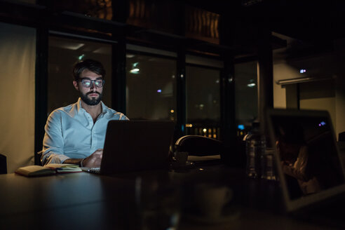 Mid adult businessman in office at night typing on laptop - CUF51366