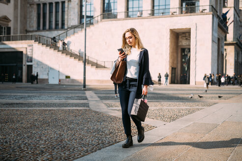 Young woman strolling in city square looking at smartphone - CUF51378