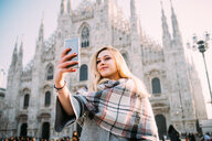 Young female tourist taking smartphone selfie in front of Milan cathedral, Milan, Italy - CUF51381