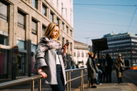 Young woman looking at smartphone at tram station - CUF51384
