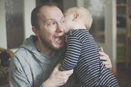 Father with open mouth holding his little son - IHF00012
