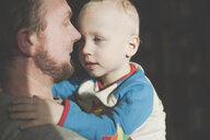 Father holding his little son in sunlight - IHF00015