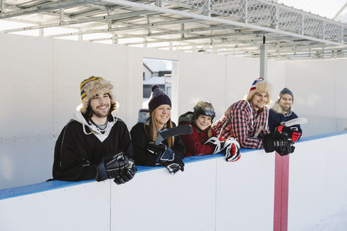 Friends watching outdoor ice hockey match from bench sideline - HEROF36198