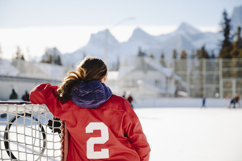 Girl playing outdoor ice hockey, resting on goal - HEROF36207