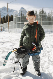 Portrait confident, determined boy with outdoor ice hockey equipment - HEROF36216