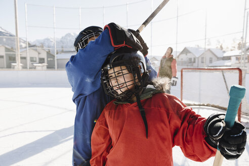 Happy friends playing outdoor ice hockey - HEROF36228