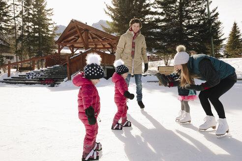 Family ice skating on frozen pond - HEROF36246