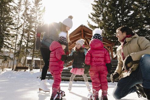 Family ice skating on sunny frozen pond - HEROF36249