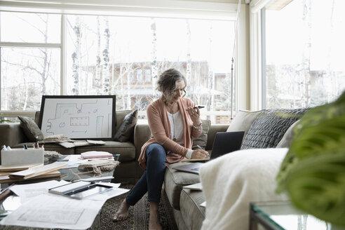 Senior female interior designer working from home, using laptop and smart phone on living room sofa - HEROF36368