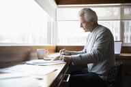 Senior man working from home, reviewing paperwork - HEROF36380