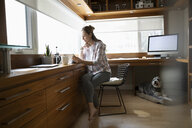 Woman working from home, using digital tablet in home office - HEROF36395