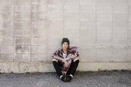 Portrait confident young female skateboarder sitting against concrete wall - HEROF36446