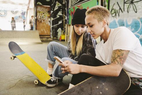 Young female skateboarders using smart phone at indoor skate park - HEROF36485