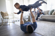 Playful father lifting son overhead in living room - HEROF36506
