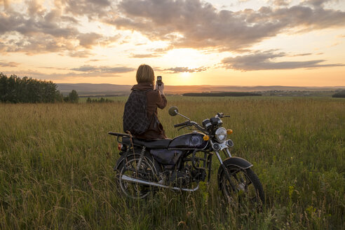 Caucasian woman with motorcycle in field photographing sunset - BLEF03251