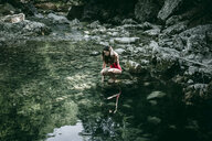 Caucasian woman crouching on rocks at pool of water - BLEF03254