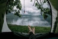 Feet on man laying in camping tent at lake - BLEF03266