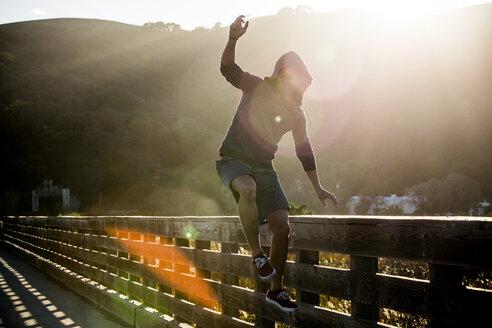 Mixed Race man jumping near railing on footbridge - BLEF03281