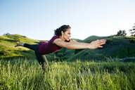 Mixed Race woman practicing yoga on hill - BLEF03311