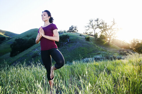 Mixed Race woman practicing yoga on hill - BLEF03314