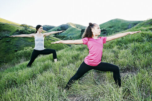 Mother and daughter practicing yoga on hill - BLEF03332