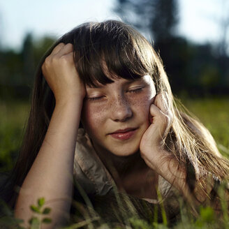 Caucasian girl with freckles laying in grass - BLEF03386