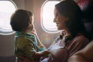 Happy mother and little daughter on airplane - GEMF02949