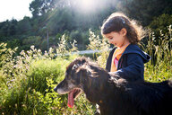 Happy toddler girl walking with dog in nature - GEMF02967