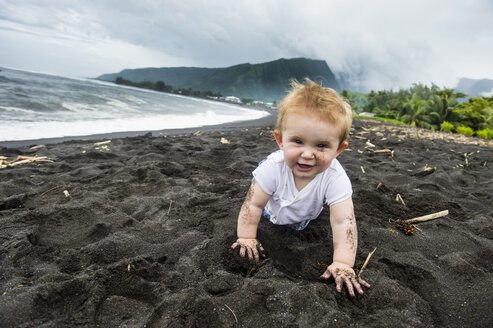 French Polynesia, Taharuu Beach, baby girl playing in black sand - RUNF02063