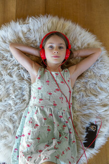 Girl lying on carpet at home listening to music with headphones and smartphone - SARF04280