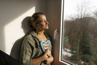 Smiling young woman at the window holding gingerbread heart - GUSF01967