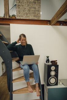 Smiling young woman sitting on stairs at home using laptop - GUSF01973