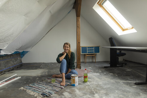 Smiling young woman sitting on the floor in attic with paint bucket - GUSF01979