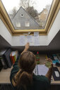 Rear view of young woman sitting at desk in attic learning - GUSF01985