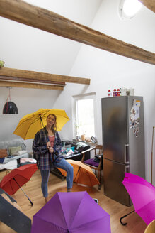 Young woman with umbrellas at home - GUSF01988