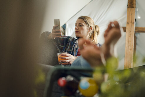Relaxed young woman sitting on couch looking at cell phone - GUSF02006