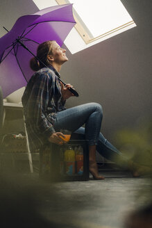 Smiling young woman with umbrella looking out of window - GUSF02009