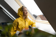 Smiling young woman in raincoat looking out of attic window - GUSF02012