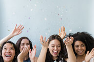 Smiling women throwing confetti - BLEF03425